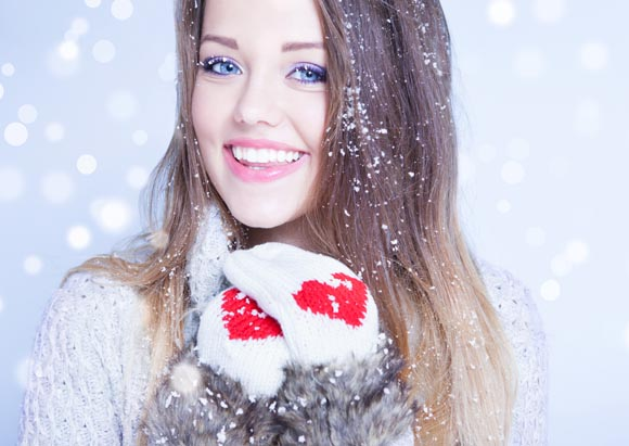 Winter face close up of young woman covered with snowflakes
